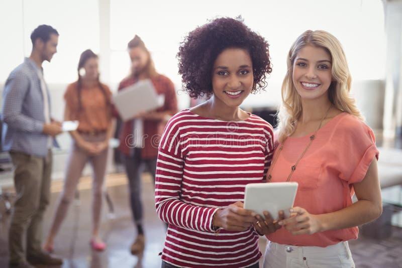 Portret żeńscy biznesowi koledzy dyskutuje nad cyfrową pastylką przy kreatywnie biurem zdjęcia stock