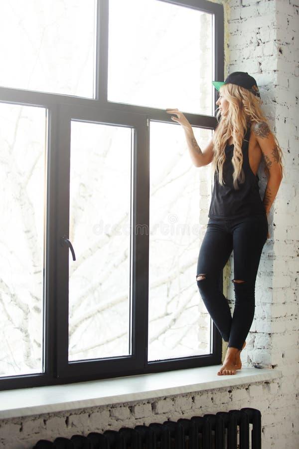 Portret żeńska blondynka stoi na windowsill blisko wielkiego jaskrawego okno w eleganckich czerni ubraniach zdjęcie royalty free