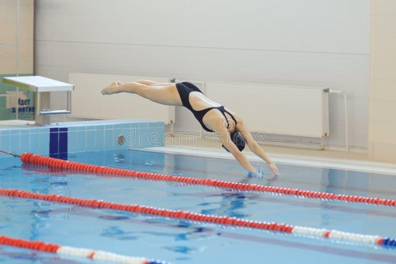 Portret żeńska pływaczka, ten doskakiwanie i pikowanie w salowego sporta pływackiego basen kobieta sporty zdjęcia stock