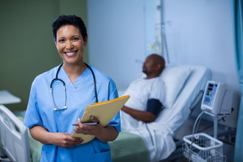 Portret żeńska pielęgniarki pozycja z kartoteką w oddziale zdjęcie royalty free