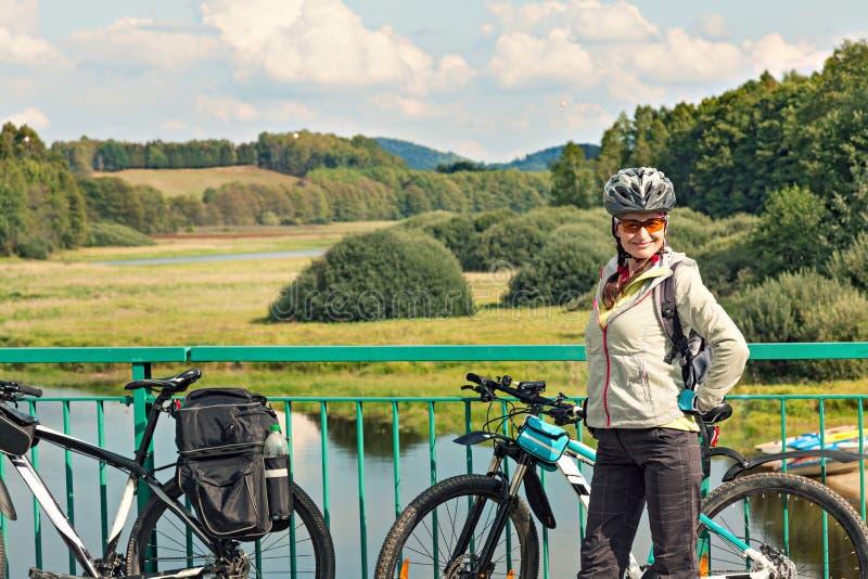 Portret żeńska turystyczna cyklista pozycja na moscie na b zdjęcia stock