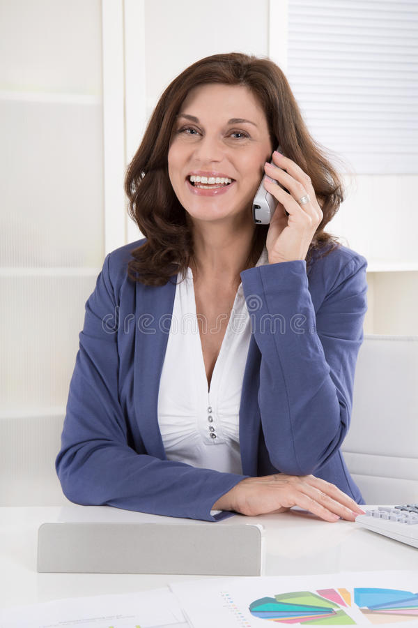 Portret żeński kierownik wyższego szczebla dzwoni przy biurkiem obrazy royalty free