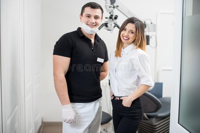 Portret życzliwy męski dentysta z szczęśliwym żeńskim pacjentem w nowożytnej stomatologicznej klinice dentyści fotografia stock