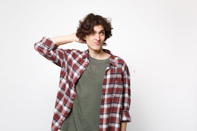 Portret absorbujący zadumany młody człowiek patrzeje na boku w przypadkowych ubraniach, stawia rękę za głową odizolowywającą na b obrazy royalty free