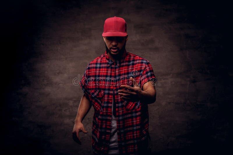 Portret afroamerykański tancerza facet ubierał w czerwonej runo nakrętce i koszula przy studiiem na zmroku fotografia royalty free