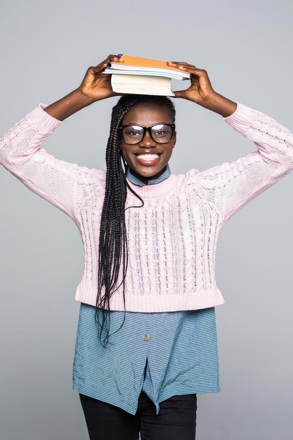 Portret afrykańska dziewczyny mienia książka na jej kierowniczym i patrzeć daleko od przy kopii przestrzenią odizolowywającą nad  obraz royalty free