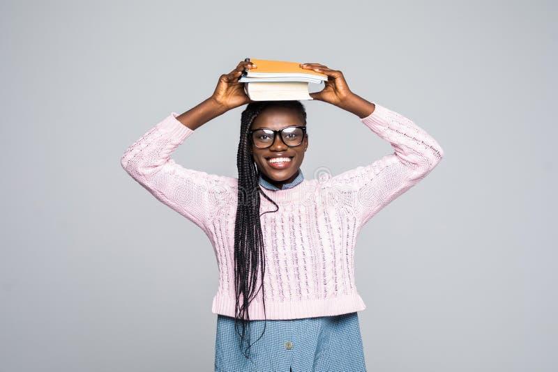Portret afrykańska dziewczyny mienia książka na jej kierowniczym i patrzeć daleko od przy kopii przestrzenią odizolowywającą nad  obraz stock