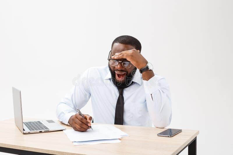 Portret afrykański mężczyzny dosypianie przy jego miejsce pracy na szarym tle obrazy stock