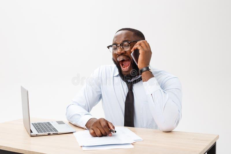 Portret afrykański mężczyzny dosypianie przy jego miejsce pracy na szarym tle fotografia stock