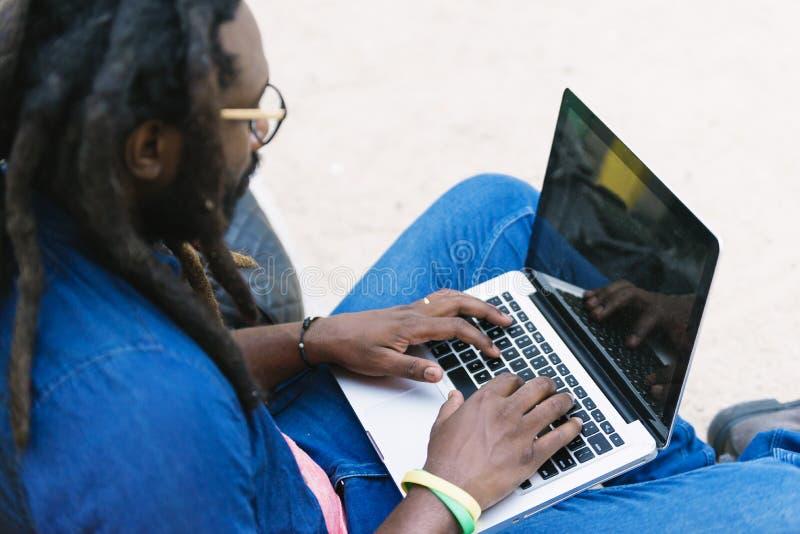 Portret afrykańskiego mężczyzna siedzący outside z laptopem zdjęcie royalty free