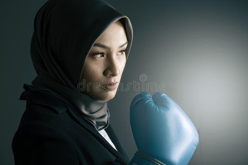 Portret agresywna i ufna wyrażeniowa młoda uśmiechający się fachowa kobieta jest ubranym bokserską rękawiczkę zdjęcia royalty free