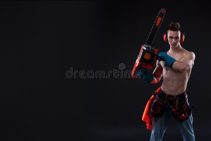 Portret agresywny mięśniowy mężczyzna z piłą łańcuchową w ręce, pozuje na czarnym tle budowniczy zdjęcie royalty free