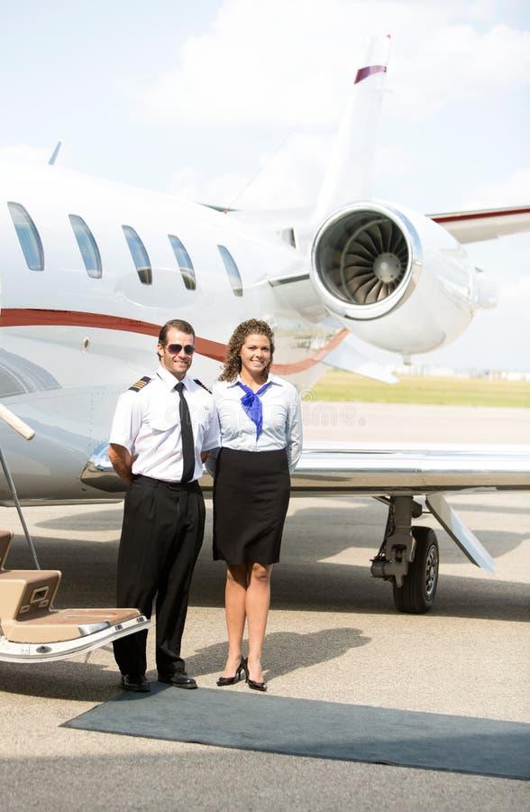 Portret Airhostess I pilota pozycja Przeciw fotografia royalty free