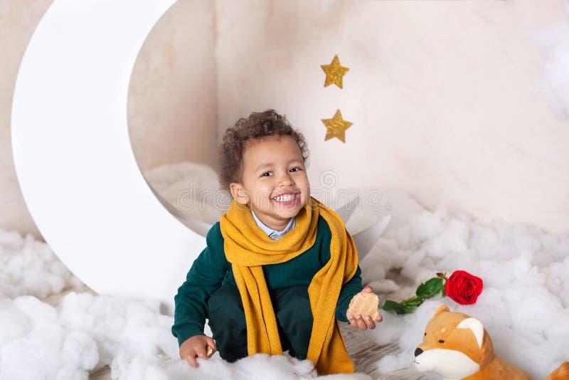 Portret amerykanin afrykańskiego pochodzenia troszkę Dziecko u?miechy Czarna chłopiec w zielonym pulowerze i żółtym szalika ono u zdjęcie stock