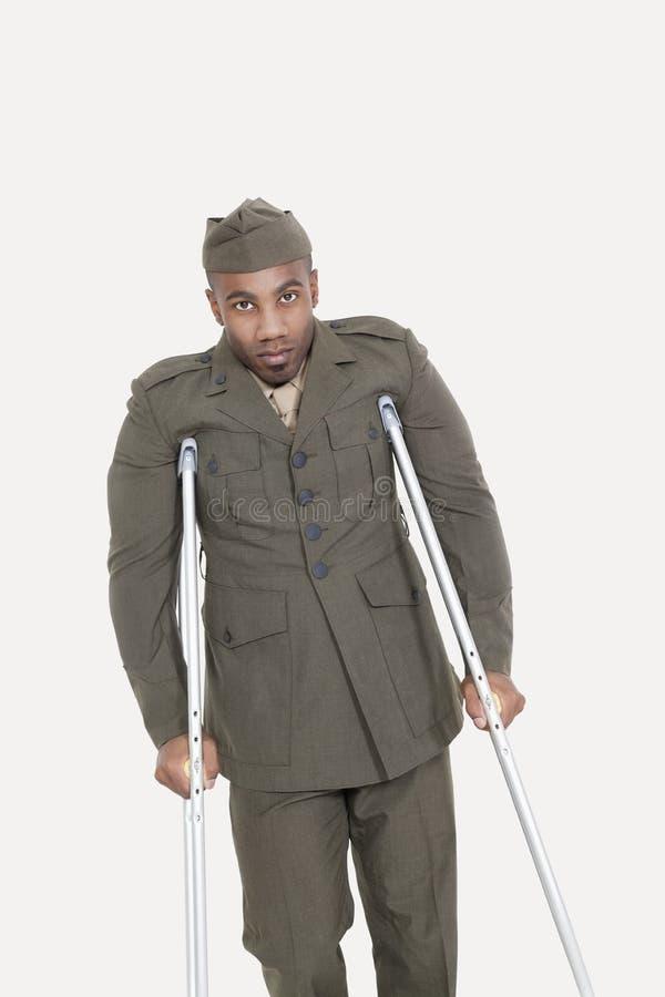 Portret amerykanin afrykańskiego pochodzenia USA oficer wojskowy z szczudłami nad szarym tłem zdjęcia royalty free