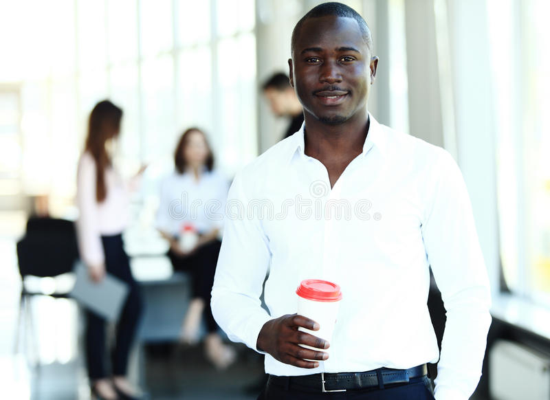Portret amerykanina afrykańskiego pochodzenia biznesowy mężczyzna z kierownictwami pracuje w tle zdjęcie royalty free