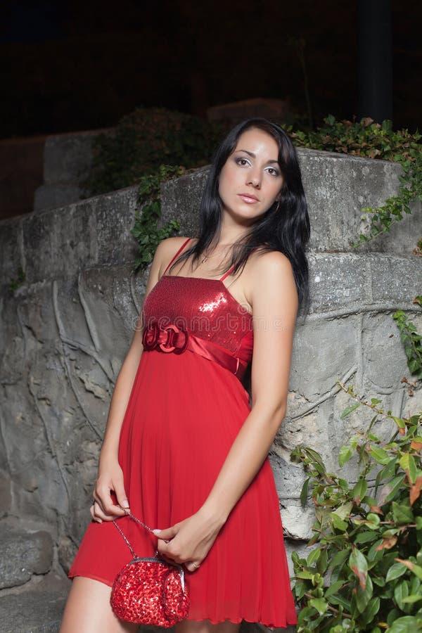 Portret atrakcyjna brunetka w czerwonych sundress w noc parku zdjęcia stock