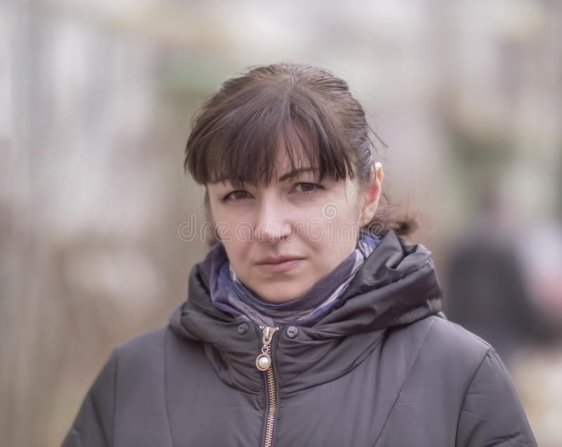 Portret atrakcyjna brunetki dziewczyna na zamazanym tle ulica, patrzeje kamerę fotografia royalty free