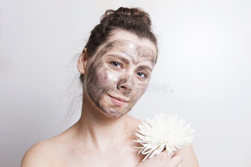 Portret atrakcyjna brunetki dziewczyna z czarną kosmetyczną twarzy maską i chwyta białym kwiatem Twarzowa maskowa skóry opieka za obraz stock