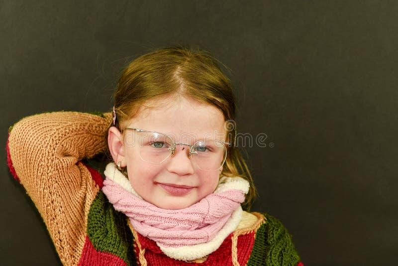 Portret atrakcyjna caucasian mała dziewczynka z eyeglasses Śmieszny śliczny uśmiechnięty dziecko patrzeje kamerę na czerni zdjęcia stock