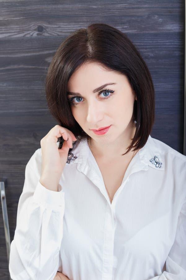 Portret atrakcyjna ciemnowłosa kobieta jest ubranym biel bluzki pozycję w biurze Zakończenie fotografia royalty free