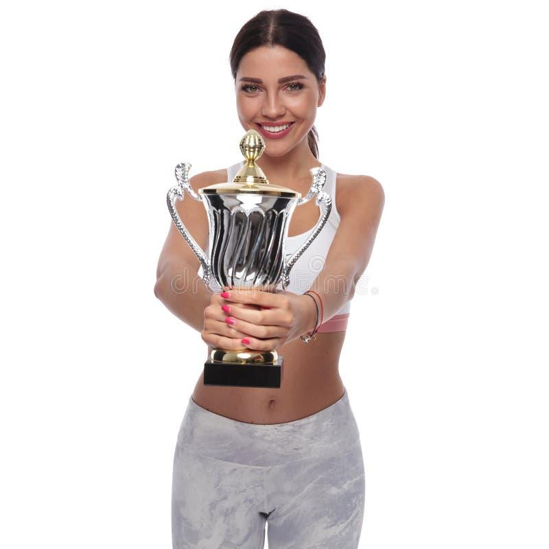 Portret atrakcyjna dysponowana kobieta oferuje ci trofeum obrazy royalty free