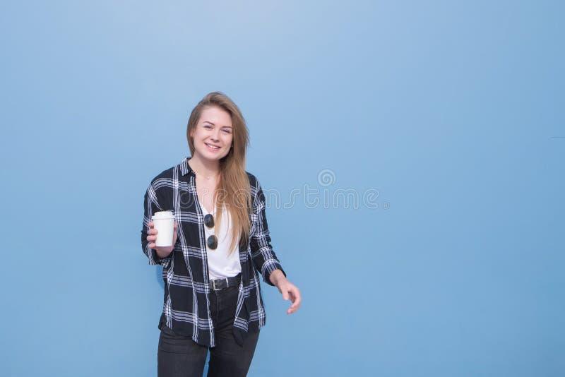 Portret atrakcyjna dziewczyny pozycja na błękitnym tle z papierową filiżanką w ona ręki i patrzeć w kamerę zdjęcie stock