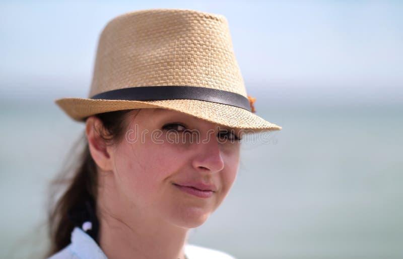 Portret atrakcyjna kobieta jest ubranym kapelusz i patrzeje kamerę, uśmiechnięty obraz royalty free