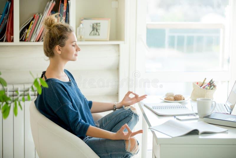 Portret atrakcyjna kobieta przy stołem, lotos poza obrazy stock