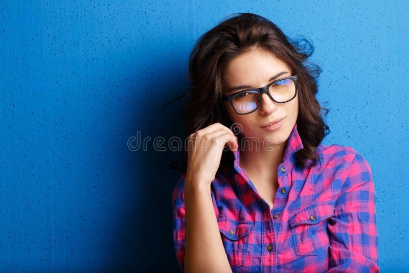 Portret atrakcyjna kobieta w szkłach na błękitnym tle obraz stock