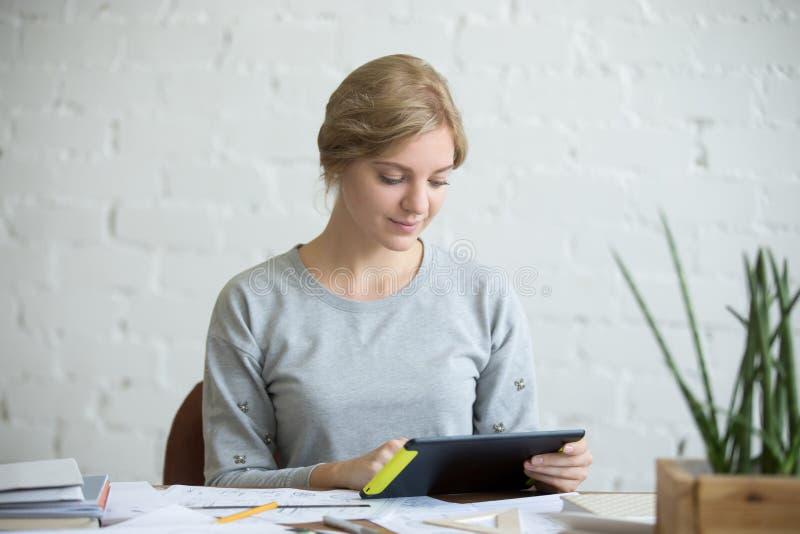 Portret atrakcyjna kobieta z pastylką przy biurkiem obrazy royalty free
