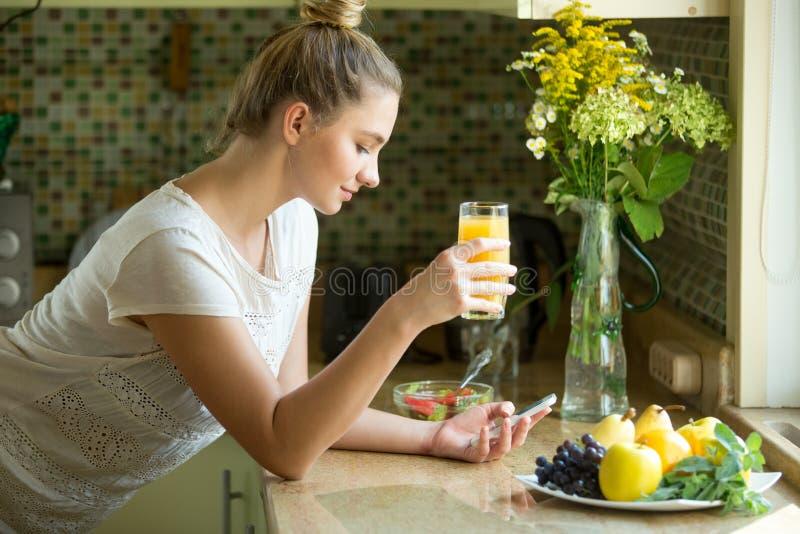 Portret atrakcyjna kobieta z sokiem i telefonem zdjęcie royalty free