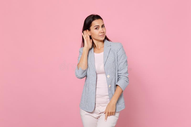 Portret atrakcyjna młoda kobieta w pasiastej kurtce podsłuchuje z przesłuchanie gestem blisko ucho odizolowywającego na różowym p obraz stock