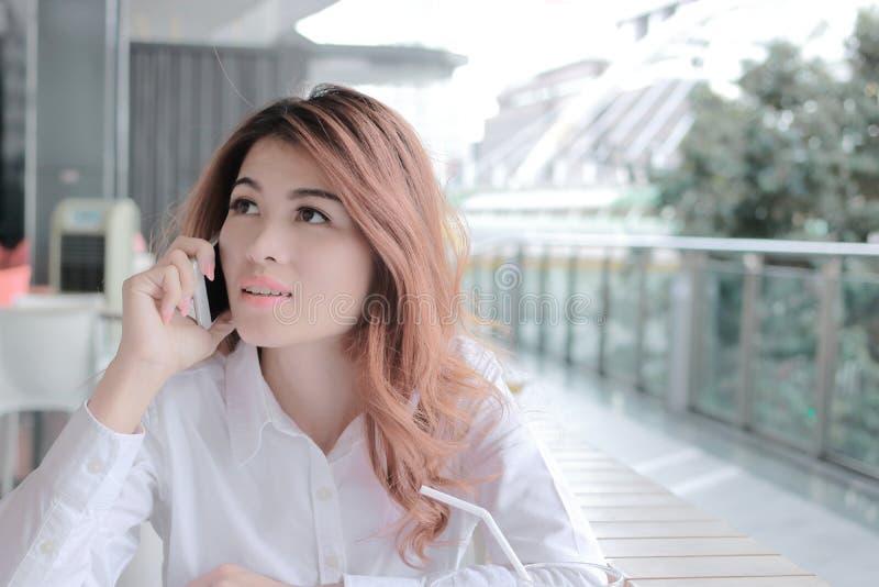 Portret atrakcyjna młoda Azjatycka biznesowa kobieta opowiada na telefonie dla jej pracy w biurze z kopii przestrzeni tłem obrazy stock