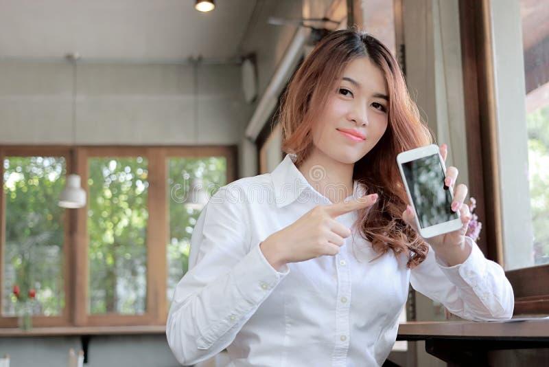Portret atrakcyjna młoda Azjatycka kobieta wskazuje mobilnego mądrze telefon z palcem przy biurem z kopii przestrzeni tłem zdjęcie stock
