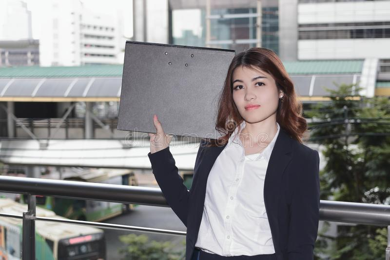 Portret atrakcyjna młoda Azjatycka sekretarki kobiety mienia dokumentu falcówka przy outside biurem obrazy royalty free