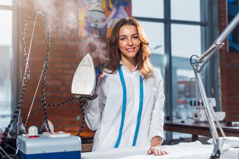 Portret atrakcyjna młoda Kaukaska brunetki krawcowej pozycja w biel ubraniach trzyma parowego żelazo w studiu obrazy royalty free