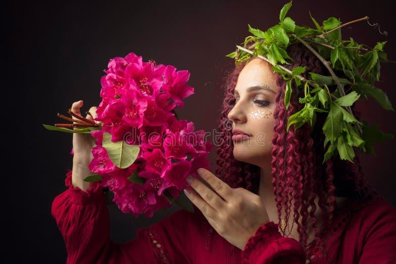 Portret atrakcyjna m?oda kobieta w czerwieni sukni z bukietem czerwony r??anecznik i wianek na g?owie fotografia stock
