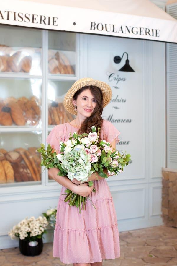 Portret atrakcyjna młoda kobieta w lato smokingowym i słomianym kapeluszu, trzyma bukiet kwiaty przeciw tłu Fren obrazy stock