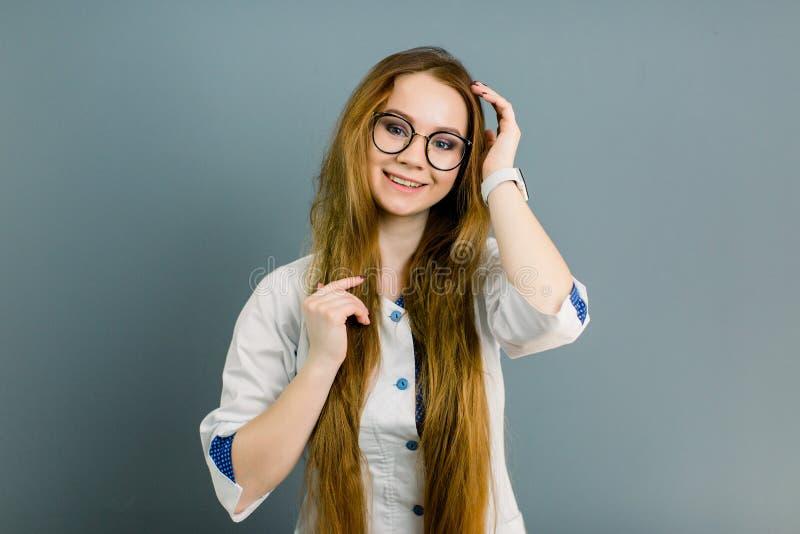 Portret atrakcyjna młoda kobiety lekarka w białym żakiecie, odosobniony na szarym tle obraz stock