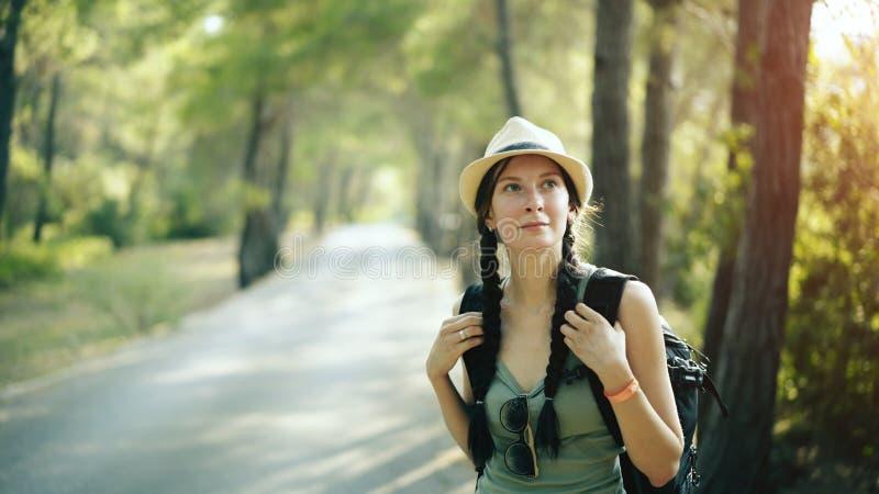 Portret Atrakcyjna turystyczna dziewczyna uśmiechnięta i patrzeje w kamerę podczas gdy chodzący pięknego las i wycieczkujący fotografia royalty free