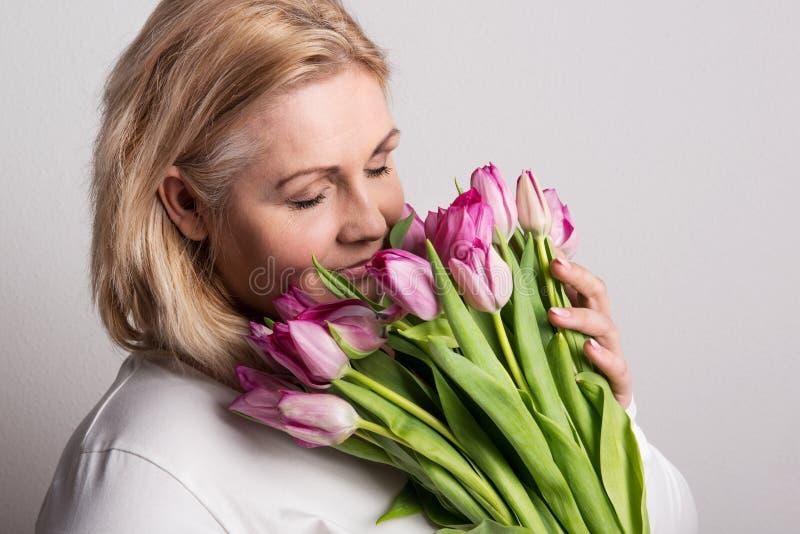 Portret atrakcyjna z nadwagą kobieta z tulipanami w studiu, oczy zamykający zdjęcie stock