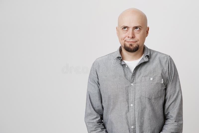 Portret atrakcyjnego łysego mężczyzna przyglądający up być rozpraszający uwagę i zadumany nad białym tłem Przystojny facet pracuj zdjęcie stock