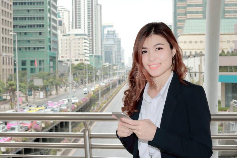 Portret atrakcyjnego młodego Azjatyckiego biznesowej kobiety mienia mobilny mądrze telefon i ono uśmiecha się przy miastowym budy obraz stock