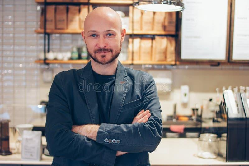 Portret atrakcyjny dorosły pomyślny łysy brodaty mężczyzna w kostiumu na cukiernianym kawa domu tle fotografia stock