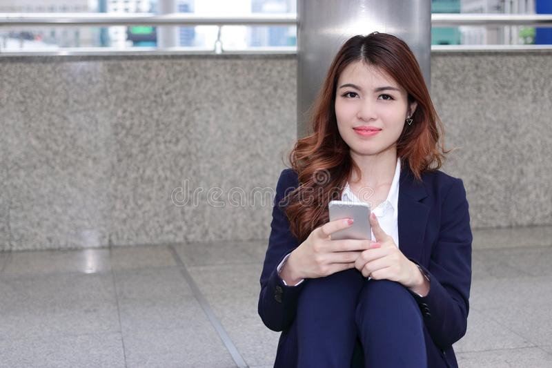 Portret atrakcyjny młody Azjatycki biznesowej kobiety obsiadanie na podłoga i mienia mobilnym mądrze telefonie w jej rękach z kop zdjęcia royalty free