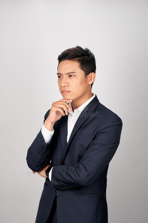 Portret atrakcyjny młody azjatykci biznesmen jest bałamutny nad białym tłem zdjęcia royalty free