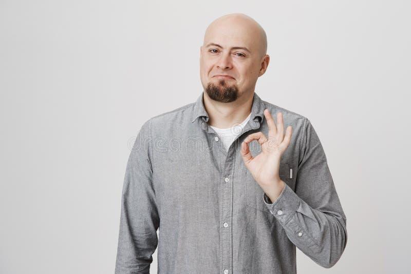 Portret atrakcyjny uśmiechnięty łysy mężczyzna z broda seansu ok znakiem i pozycja z złym wyrażeniem nad szarość zdjęcie stock