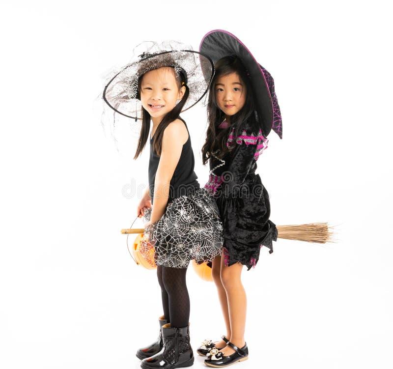 Portret Aziatische meisjes in Halloween-kostuum die de bezem berijden toget royalty-vrije stock afbeelding