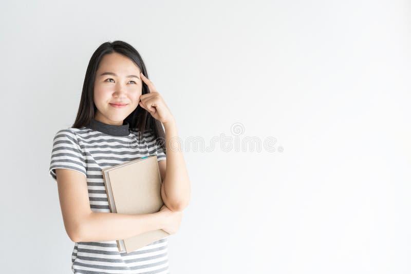 Portret Aziatische vrouw die en notitieboekje op witte ruimte denken houden als achtergrond en exemplaar royalty-vrije stock afbeeldingen